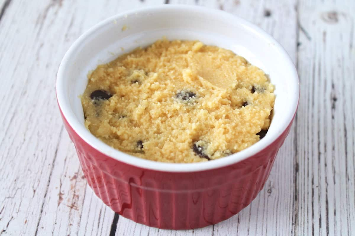 Uncooked chocolate chip mug cake batter in a red ramekin on a white wooden surface