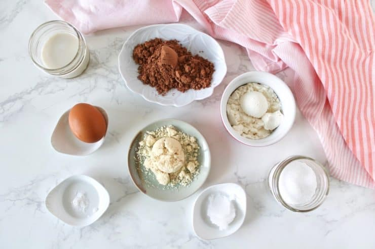 Overhead shot of protein mug cake ingredients in various dishes on a white marble surface next to a pink and white striped dish towel