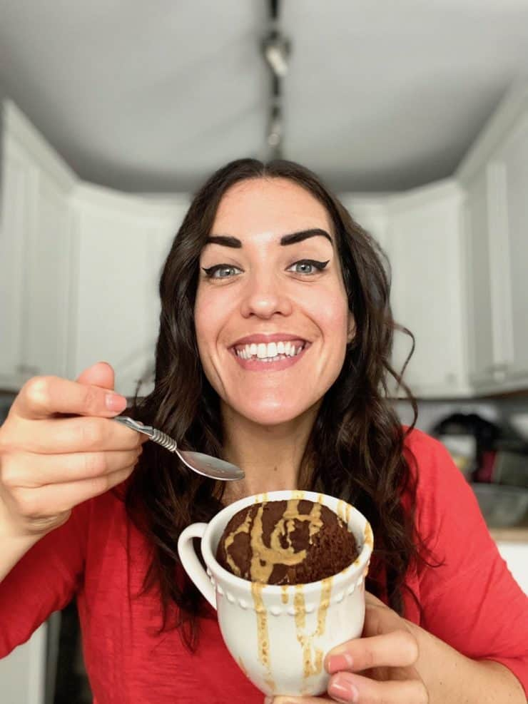 Smiling dark haired woman with red shirt on holding mug cake with spoon in other hand