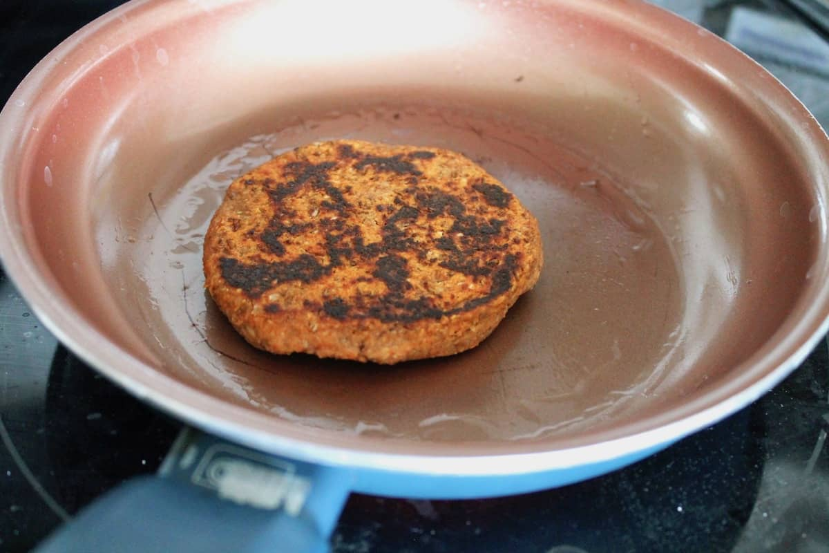 Lentil patty with some black charring on top in an orange skillet