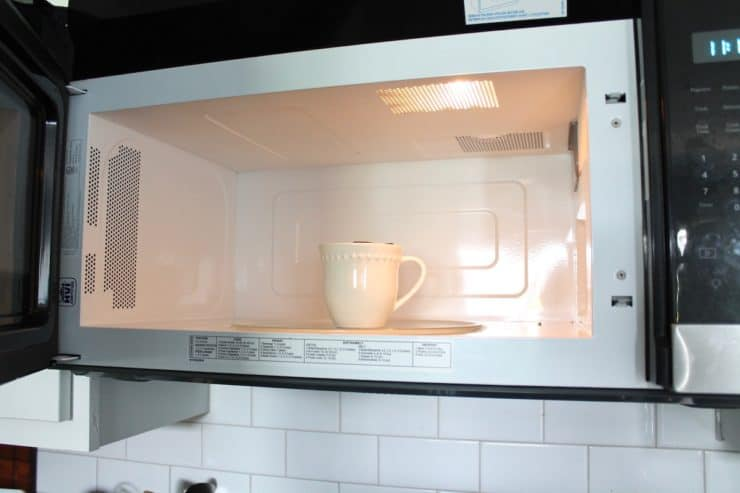 Microwave with an open door with a white mug inside it