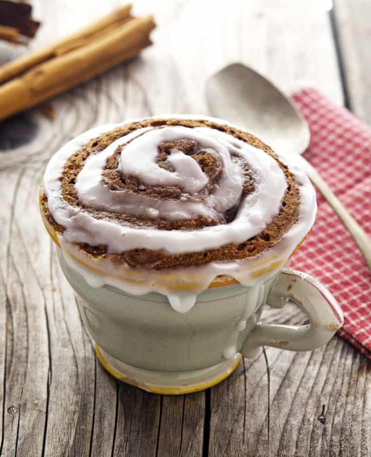 Mug filled with cinnamon cake with white frosting in a swirl design on top on a wooden table next to a red and white checkered dish towel with a spoon on it next to cinnamon sticks