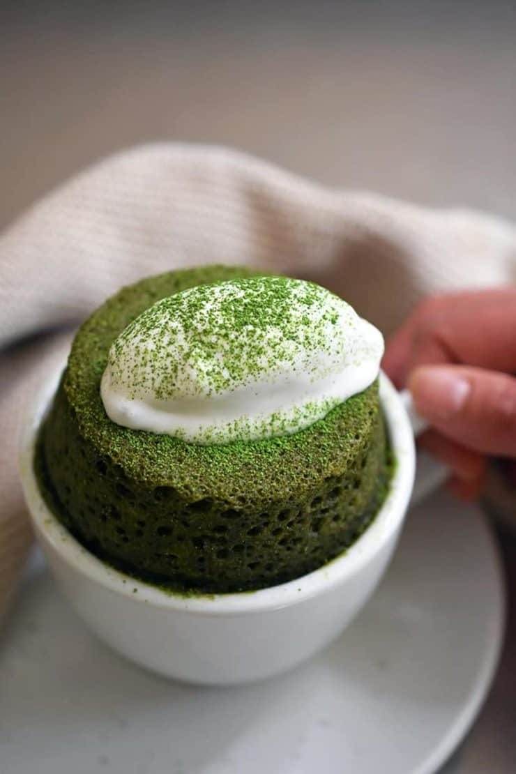 Hand holding a small white tea cup with green matcha cake inside with a dollop of white whipped cream on top sprinkled with green matcha powder next to a white dish towel