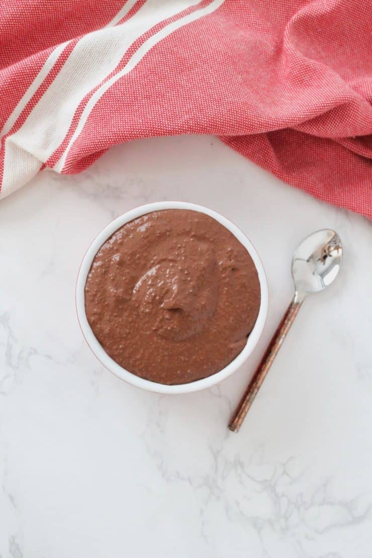 Overhead shot of red ramekin filled with chocolate chia pudding on white marble surface next to spoon and red dish towel