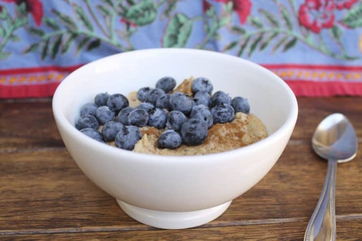 White bowl filled with paleo oats topped with blueberries and cinnamon on a wooden surface next to a spoon with a floral cloth in the background