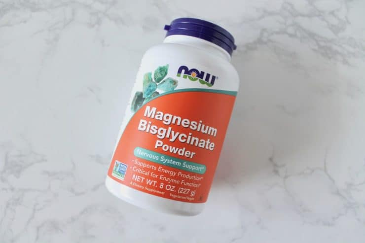 Orange and white supplement bottle of magnesium on a white marble surface
