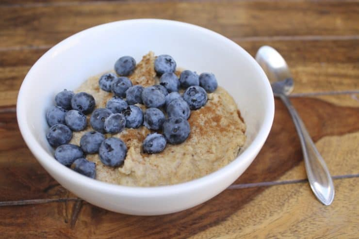 Close up of a white bowl filled with paleo oats topped with blueberries and cinnamon on a wooden surface next to a spoon