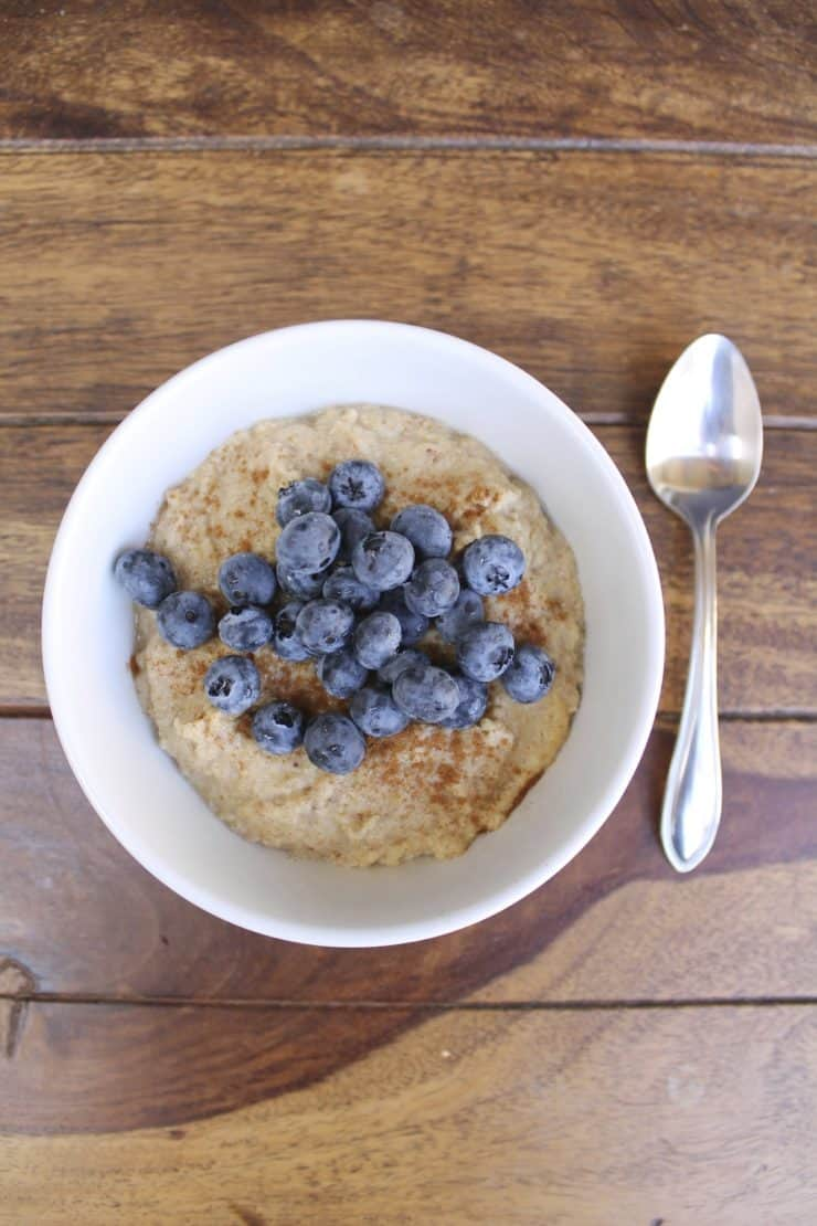 Overhead shot of a white bowl filled with paleo oatmeal topped with blueberries and cinnamon on a wooden surface next to a spoon