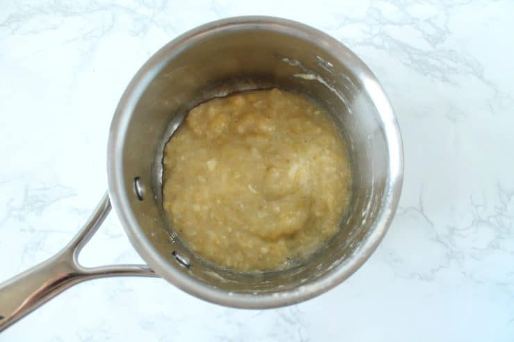 Stainless steel saucepan with mashed up banana inside on a white marble surface