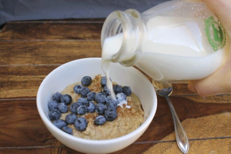 White bowl filled with paleo oatmeal topped with blueberries and cinnamon on a wooden surface with a hand pouring milk onto the oats out of a glass milk jug