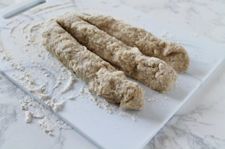 three thick ropes of bread dough in a line on a floured surface