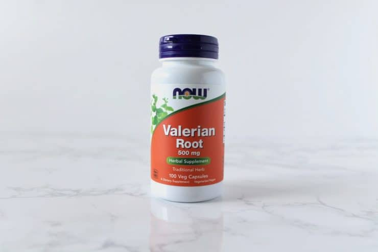 Orange and white supplement bottle of valerian root on a white marble surface